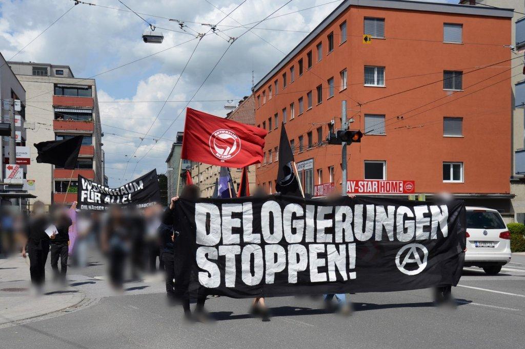 """Ansicht der Demo, wie sie durch Lehen zieht. Neben dem Front-Transparent mit Anarchie-A und """"Delogierungen stoppen!"""" sieht man wieder viele Fahnen, ein Hoch-Transparent mit der Aufschrift """"Wohnraum für alle!"""" und eineverpixelte Menschenmenge."""